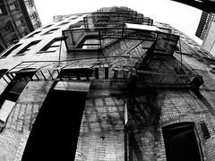 Old Building Fire Escape (MassiveKontent) Tags: streetphotography montreal bw contrast city monochrome urban blackandwhite street photo montréal quebec photography bwphotography streetshot architecture asphalt concrete shadows noiretblanc blancoynegro gppro fireescape steps urbandecay