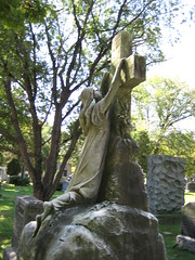 Mourner Statue Hanging From Cross Grave 0889 (Brechtbug) Tags: mourner statue hanging from cross grave memorial tomb profile graveyard marble cemeteries nyc monument cemetery woodlawn horn tombstone crypt standing holding hands bronx new york city photographed 2007