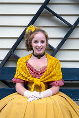 A young actress waiting to perform at Barkerville (Antonio Cangiano) Tags: barkerville britishcolumbia canada ca woman girl female femalemodel blonde blondehair redhead costume dress vintage vintagefashion portrait portraiture portraits portraitphotography streetphotography street smile smiling pretty cute beautiful actress okanaganphotographer bc history canadianhistory historic historicalsite reenactment