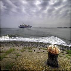 At Terneuzen the navigable waterway runs just below the coast. (Luc V. de Zeeuw) Tags: bollard cgm cma clouds cloudy coast container fairway sea ship water terneuzen zeeland netherlands