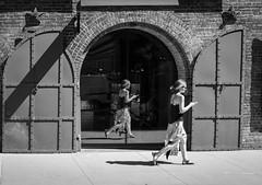Double Take (John St John Photography) Tags: brooklyn empirestores dumbo newyorkcity newyork streetphotography candidphotography youngwoman reflection brickwork castiron doors bw blackandwhite blackwhite blackwhitephotos johnstjohnphotography