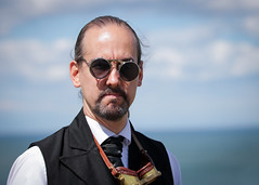 Portrait from the Whitby Steampunk Weekend IV - Days Like These (Gordon.A) Tags: yorkshire whitby steampunk whitbysteampunkweekend iv dayslikethese wsw july 2018 convivial creative costume culture lifestyle style street festival event streetevent eventphotography day sky skyline amateur streetphotography pose posed glasses goggles portrait streetportrait man colourportrait colourstreetportrait naturallight naturallightportrait digital canon eos 750d sigma sigma50100mmf18dc