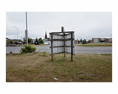 Rear of sign (Richard C. Johnson: AKA fishwrapcomix) Tags: leicaq leitz28mmsummiluxf17 color outdoor economicdownturn thegreatrecession church steeple litter sunsetsinthewest civisromanussum spqr road theamericancentury paxamericanus lightpole cars shrub weeds text sign asphalt fence utilitypole grass thelandunloved landscapeofdecline watertower trees superior wisconsinsunsetsinthewest icamesofarforbeauty sictransitgloriamundi