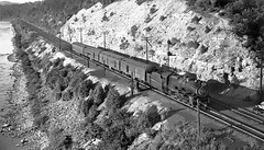 Pennsylvania Railroad K4 Pacific 4-6-2 steam locomotive # 3754, is seen while leading a passenger train on the mainline along a river bank, ca early 1940's (alcomike43) Tags: pennsylvaniarailroad prr railroads trains tracks rightofway mainline ballast roadbed conventionaljointedsectionrail ties rails bladesemaphoreblocksignal passengertrains rpo baggagerailwayexpresscar combinebaggagecoach coach heavyweightpassengercars river water steam coal smoke engine locomotive steamengine steamlocomotive k4 pacific 462 3754 engineer cab photo photograph negative bw blackandwhite old historic vintage classic