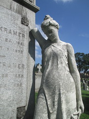 Standing Mourner Next to Tombstone Holding Lily 7699 (Brechtbug) Tags: standing mourner next tombstone greenwood cemetery statue wings graveyard tomb crypt mausoleums angels posed green wood brooklyn new york city 2018 nyc 08122018 wreath holding lily flower