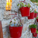 Red flower buckets hanging on hooks on a wall thumbnail