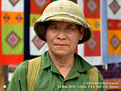 2018-03d Northeast Vietnam (60) (Matt Hahnewald) Tags: matthahnewaldphotography facingtheworld character head face eyes expression shaved beardless hat pithhelmet army military veteran olive shirt uniform green respect dedication commitment traditional cultural market bazaar tuesday weekly village cocly laocai vietnam northern vietnamese male man detail background nikond3100 primelens nikkorafs50mmf18g 50mm horizontal street portrait headshot outdoor posing authentic manly elderly clarity fullfaceview 1200x900pixels resized colour person conceptual 4x3ratio closeup consensual lookingcamera worn