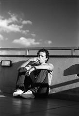 Portrait on roof (bruscwillis) Tags: nikon f5 agfa apx 100 tmax dev iso plustek 8100 man porrtait roof clouds sky jeans shoes sunny film 35mm blackwhite bw black white monochrome red filter hoya 25a