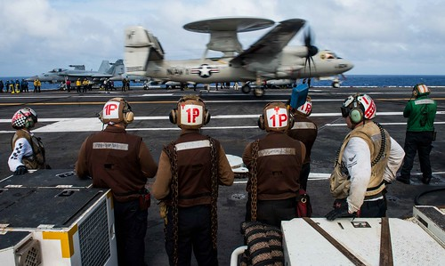 Sailors observe as an E-2D Hawkeye lands on the flight deck.