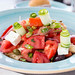 Greek salad with tomato, cucumber, dry onion, sun-dried tomato, feta cheese, capers and olive oil