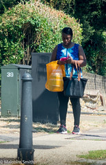 Modern Communication 25 (M C Smith) Tags: woman bag orange phone pink black pentax k3ii blue walking hedge green bollard pavement grass telecoms box wall brick shadows numbers letters