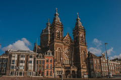The Basilica of St. Nicholas (Mark Liddell) Tags: amsterdam holland thenetherlands netherlands nederlands capital city europe travel water river canal dutch architecture buildings sunset windows cathedral church rose window stained glass blue sky outdoors