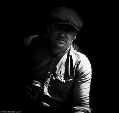 A Peaky Blinder. (Neil. Moralee) Tags: neilmoralee steamrally2018neilmoralee man face portrait dark dim shadow cap flat hat peaky blinder candid steam vintage rally norton fitzwarren somerset black white bw bandw blackandwhite mono monochrome neil moralee olympus omd em5 contrast strong harsh britain england
