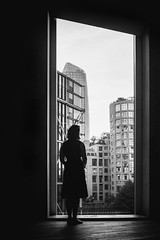 The best view. (markfly1) Tags: tate modern art gallery street candid huge window woman looking through large girl wistful gazing skyscrapers high buildings frame off centre black white baw bw mono monochromatic grain grainy grey shades textures windows glass silhouetted figure image photography nikon d750 35mm manual focus lens