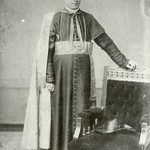 Unidentified priest positioned beside chair, front facing, full-length portrait thumbnail