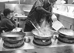 Thats Steaming Hot To Trot (tcees) Tags: soho london w1 shop man woman people wok cooking ladel water jug steam food gloves takeaway kitchen night x100 fujifilm finepix streetphotography street bw mono monochrome blackandwhite cap eating urban noodles
