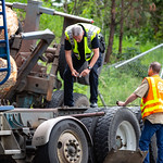 Police officer inspects damage on logging truck after accident. June 2018 Everett Washington. thumbnail
