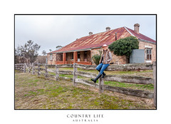 Country woman sitting on fence of old rustic farm house (sugarbellaleah) Tags: woman rurallife rural homestead farm female countryside countrylife outback farmhouse fence rustic abandoned old ancient adult smiling carefree lifestyle relaxedjeans hat akubra cobblestone tinroof corrugatediron outdoors thisisaustralia cheerful farmlife boots cold watertank