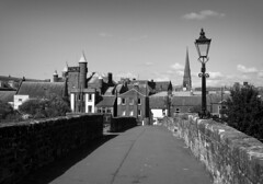 Devorgilla Bridge (Rollingstone1) Tags: devorgillabridge bridge dumfries scotland pedestrian buildings architecture history historical city town urban blackandwhite mono bw art artwork light lamp wall spire trees road monochrome sky tower