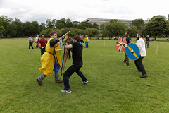 Historia Normannis Meadows June 2018-515 (Philip Gillespie) Tags: historia normannis central scotland sparring fighting shields swords axes spears park grass canon 5dsr men man women woman kids boys girls arms feet hands faces heads legs shins running outdoor tabards chain mail chainmail helmets hats glasses sun clouds sky teams solo dead act acting colour color blue green red yellow orange white black hair practice open tutorial defending attacking volunteer amateur kneeling fallen down jumping pretty athletic activity hit punch
