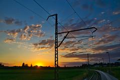 Sunset at a railway stop (echumachenco) Tags: sunset sky sun cloud railway tracks station freilassinghofham summer july berchtesgadenerland bavaria bayern germany deutschland nikond3100 freilassing grass pylon lines