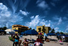 Sky Rage (Andy Zito) Tags: sky rage deep blue skies white puffy clouds wonderful beach hollywood umbrellas goers swim trunks bikinis lathering up suntan lotion applying reading book