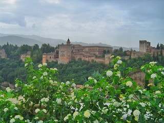 Looking up from the beautiful Arabic barrio called the Albaicín, you can see the majestic walls of the Alhambra! A palace and fortress complex located in Granada, Spain. The fortress has the backdrop of the Sierra Nevada Mountains in the background! This
