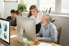Smiling young manager helping senior worker with computer office work - Credit to https://www.lyncconf.com/ (nodstrum) Tags: work home time today hardwork working workethic homework officework cubicle workplace money jobs networking desk