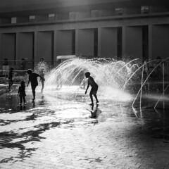Independence Day Fountain Play (iMatthew) Tags: boston ma concert blackandwhite bw olympuspenf olympuspen penf sun illumination fountain christiansciencecenter backbay kidsatplay silhouette lateafternoonsun