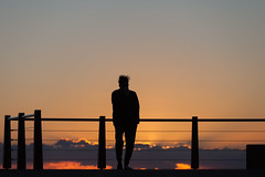 Watching the sunrise (Mikey Down Under) Tags: asian australia australian coast coffee coffs cold dawn daybreak drink hair headland japanese man northcoast northern nsw ocean orange pacific silhouette silhouetted standing sunrise watching woolgoolga
