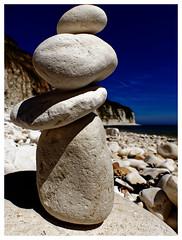 rock pile (Mallybee) Tags: pebbles landscape sky blue beach cliffs rocks panasonic mallybee f28 1235mm lumix dcg9 g9