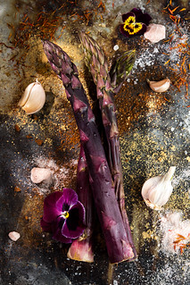Purple asparagus flat lay. Garlic spices violet flower over on rustic background. Vegetarian dieting organic healthy eating concept.