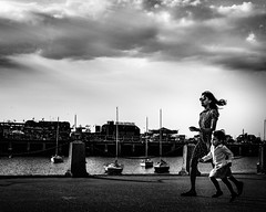 The great race (Kieron Ellis) Tags: coast port sea boats people woman girl child running light shadow contrast sunglasses candid street blackandwhite blackwhite monochrome