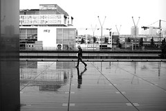 Crossing the wet square (pascalcolin1) Tags: paris13 bnf homme man pluie rain reflets reflection photoderue streetview urbanarte noiretblanc blackandwhite photopascalcolin 50mm canon50mm canon