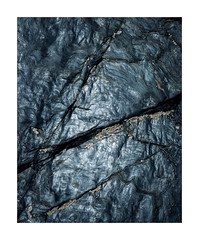 Rock Study 4 (Dave Fieldhouse Photography) Tags: rocks rockstudy closeupphotography abstract intimate fracture life patterns contours texture beach sea coastal coast cornwall cloudy fujifilm fuji fujixpro2 wwwdavefieldhousephotographycom black reflection sheen gloss shiny smooth shells