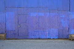 The corrugated blues (James_D_Images) Tags: alley shop corrugated sheet metal building blue blues door concrete foundation street asphalt abstract architecture painted damaged dented aged faded lines pattern eastvancouver