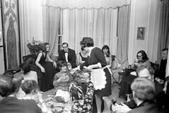 040271 23 (ndpa / s. lundeen, archivist) Tags: nick dewolf nickdewolf blackwhite monochrome blackandwhite 35mm film photographbynickdewolf bw 1971 1970s boston massachusetts social socializing party formal blacktie blacktieaffair people livingroom furniture windows curtains drapes woman women sittingonthefloor seated sitting floor onthefloor man men suit suits tie bowtie dress dresses food plates cigarette smoker smoking maggie nancymacmillan maid maidsoutfit danielmacmillan sudieschenck connaughtmahony coffeecups glasses eyeglasses chair couch sofa may