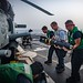 Sailors load an AGM-114 Hellfire missile onto an MH-60R Sea Hawk helicopter.