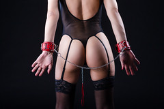BDSM Concepts and Ideas. Sexy Buttocks of Mature Caucasian Female Posing with  Accessories for Sado-Masochism Play. Tied with Chain and Wristbands. Against Black. (DmitryMorgan) Tags: 3545years alluring attractive belts blackbackground chain control darkness design desire enice erotic fantasy feelings female fetish glamour isolated lash latex leather lingerie loneliness long mature model mystery one paddle pain playful pose posing pressure provocative role sadomasochism seductive sensual sextoys sexy skirt slim subculture woman wristbands