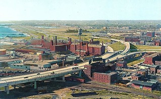 Now THIS is a rare one! The brand new Connecticut Turnpike in New Haven cutting through the freshly landfilled Long Wharf area by Long Island Sound looking west. The large factory is the old Sargent Hardware plant. 1958