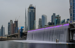 City Falls... (Aleem Yousaf) Tags: desert city falls waterfall artificial dubai cityscape architecture nikon d810 nikkor photogrpahy photo walk dusk bay downtown sheikh zayed united arab emirates design burj khalifa canal style shore water waterfront real estate longexposure sunset hazy outside skyline skyscraper tall travel world neutral density filter building middle east gulf digital panorama vantage ghost town steel buildings bridge