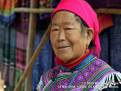 2018-03d Northeast Vietnam (21) (Matt Hahnewald) Tags: matthahnewaldphotography facingtheworld character head face eyes expression tribal attire embroidery clothes clothing garment collar consent concept humanity travel tourism culture tradition anthropology ethnic minority hilltribe rural traditional cultural market tuesday cocly laocai northern vietnam vietnamese hmong asia asian individual oneperson female woman photo detail physiognomy nikond3100 primelens 50mm 4x3 horizontal street portrait closeup headshot outdoor color authentic smiling smilingeyes headscarf elderly background wrinkles nikkorafs50mmf18g twothirdview posingcamera lookingcamera living clarity