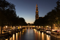 Amsterdam at night (Adrià Páez) Tags: amsterdam night canal water church tower clock westerkerk architecture religion christian protestant long exposure light boats bridge street trees capital city the netherlands nederland holland noordholland northholland europe sky canon eos 7d mark ii