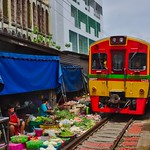 Mae Klong railway market with passing train in Samut Songkhram province in Thailand thumbnail