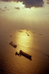 south china gold (Ron Layters) Tags: golden sea southchinasea haze smog sun sunset water boats ripples yellow taknfromtheair singapore asia slidefilmthenscanned slide transparency fujichrome velvia leica r6 leicar6 ronlayters tankers above reflection silhouette