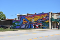 Mural on Route 66 in Waynesville, Missouri (Adventurer Dustin Holmes) Tags: 2018 missouri ozarks outdoor route66 missouri66 us66 springfield springfieldmo springfieldmissouri greenecounty downtown urban mural art artwork streetlight streetlamp lamppost awning greenawning business businesses motorcycle bridge canoe aluminumcanoe eclecticoriginals car vehicle classic sidewalk giftshop locallymadegifts sign bikerack banner 175years