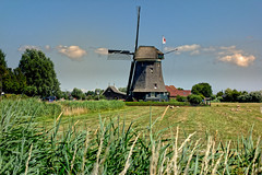 The Red Crossed Windmill (Alfred Grupstra) Tags: windmill ruralscene agriculture field farm nature landscape sky old netherlands summer grass history nonurbanscene cultures outdoors blue europe famousplace dutchculture