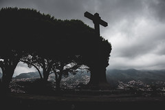 Pico dos barcelos. Watching over Funchal, as dark clouds envelope the city this cross blesses the city. (adil.baddaje) Tags: madeira portugal picodosbarcelos cross blackandwhite valley city mountain moody mist clouds tree dark art
