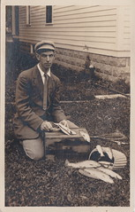 """NW Traverse City MI RPPC c.1910 VERY RARE Orson PECK with RARE Photographers Stamp on Rear Real Photographic RPPC Handsone Young Man CLEANING FISH ON TOP OF A CHERRY LUG (UpNorth Memories - Donald (Don) Harrison) Tags: vintage antique postcard rppc """"don harrison"""" """"upnorth memories"""" upnorth memories upnorthmemories michigan history heritage travel tourism restaurants cafes motels hotels """"tourist stops"""" """"travel trailer parks"""" cottages cabins """"roadside"""" """"natural wonders"""" attractions usa puremichigan """" """"car ferry"""" railroad ferry excursion boats ships bridge logging lumber michpics uscg uslss"""