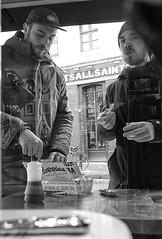 You Want My Chips ? (tcees) Tags: poppies hanbury st london e1 fishchips spitalfields x100 fujifilm finepix bw mono monochrome blackandwhite urban man streetphotography street food vinegar building window shop bicycle road kerb cap reflection hat